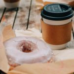 delicious donut and takeaway coffee placed on wooden surface